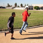 Miguel running on a track alongside a JNCS staff member in a red shirt