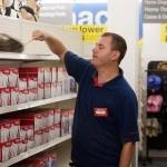 John dusting shelves at the pharmacy where he works