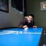 Miguel playing on a blue air hockey table
