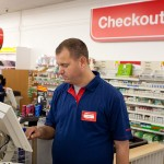 John working at the cash register at his workplace at a pharmacy