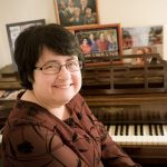 Ilene smiling while sitting next to a piano with lots of family photos on top