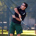 Matt playing tennis in a dark blue shirt and green shorts