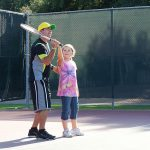 Matt teaching a little girl how to hold the tennis racket correctly for a serve