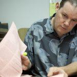 Rob in a Hawaiian shirt reviewing paperwork at the office