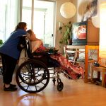 Barbara tending to a woman in a wheelchair in a living room