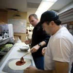 Nick spreading tomato sauce on a pizza at a pizzeria while an employee teaches him