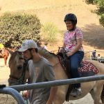 Jennifer riding a light brown horse while a man in a grey shirt holds the reins