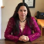 Luz Chavez sitting at a desk