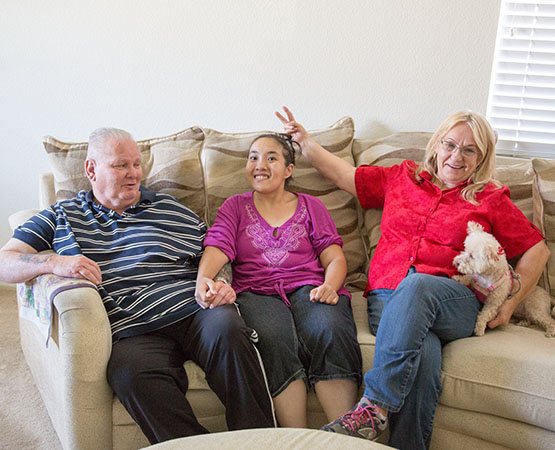mother, father, and daughter sitting on a couch together