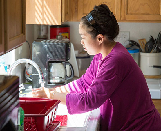 Supported individual washing her hands at the sink in her kitchen