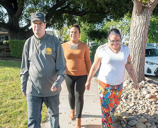 Two JNCS staff and supported individual taking a walk down the sidewalk