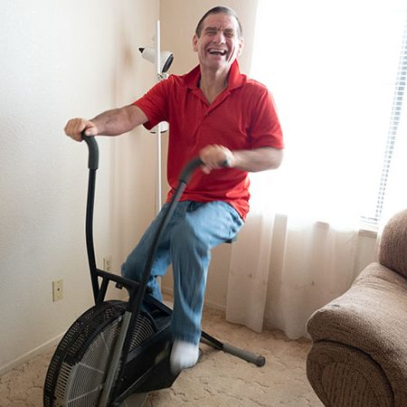 Supported individual using an exercise bike in his own home