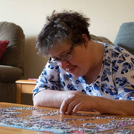 Woman working on a jigsaw puzzle at a table
