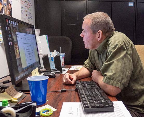 Rob examining a computer screen at the office