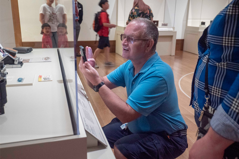 James taking a photo of something in a museum case at a gallery