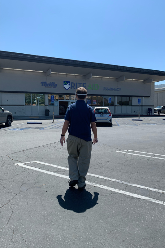 James walking through a parking lot toward RiteAid