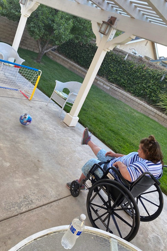 Debbie practicing soccer in a wheelchair in the backyard of her house.