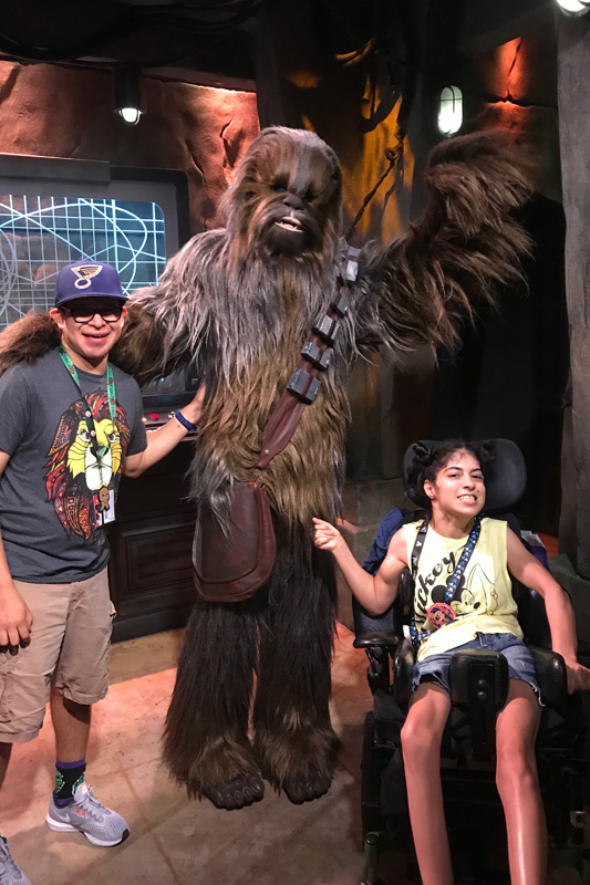 Jeff and Kimi posing with Chewbacca at an amusement park