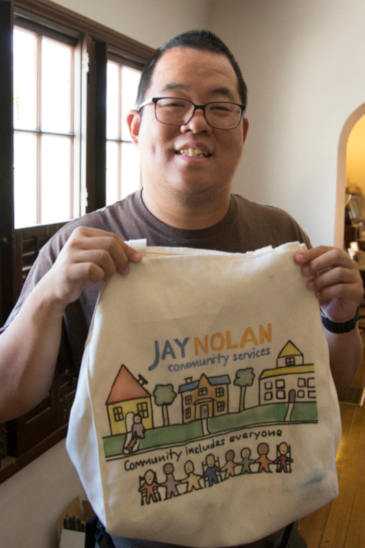 Hunter holding up a Jay Nolan Community Services tote bag her printed