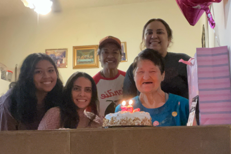 Valerie and four friends smiling next to a lit birthday cake