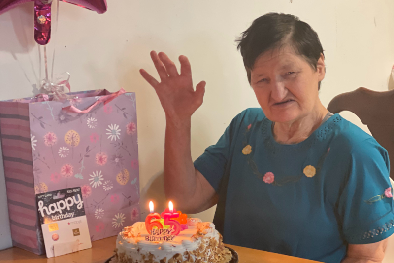 Valerie waving her hand at the camera next to a birthday cake and gift bag