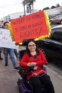 """Mariela attending a rally for disability rights wearing a red long-sleeve shirt and holding a sign that says """"#Keep the promise to fund my human rights!"""""""