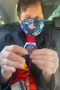 Val in a floral face mask holding up a sticker that says 'I got my COVID-19 vaccine""