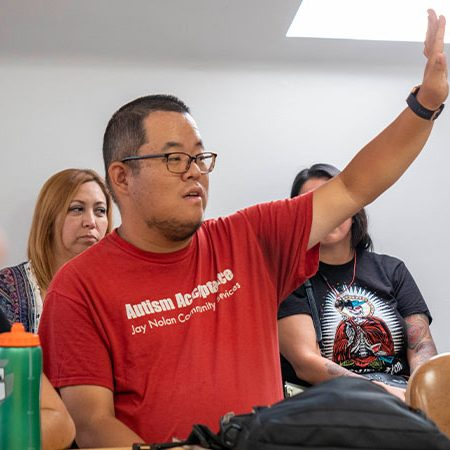 Hunter raising his hand at a meeting while wearing an Autism Acceptance shirt