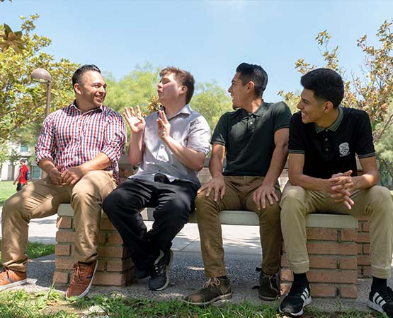 Four university students sitting on a bench together and laughing