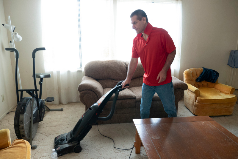 Supported Living client vacuuming his living room