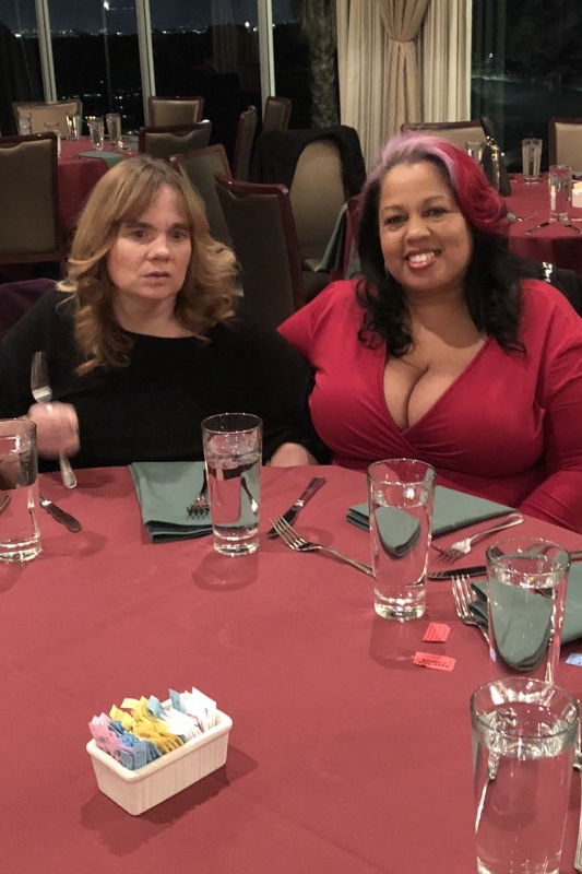 DSP Cecilia and supported individual sitting together at a holiday party