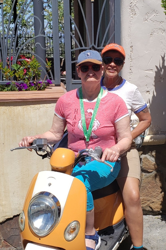 DSP Santda and supported individual Val riding a motorized scooter