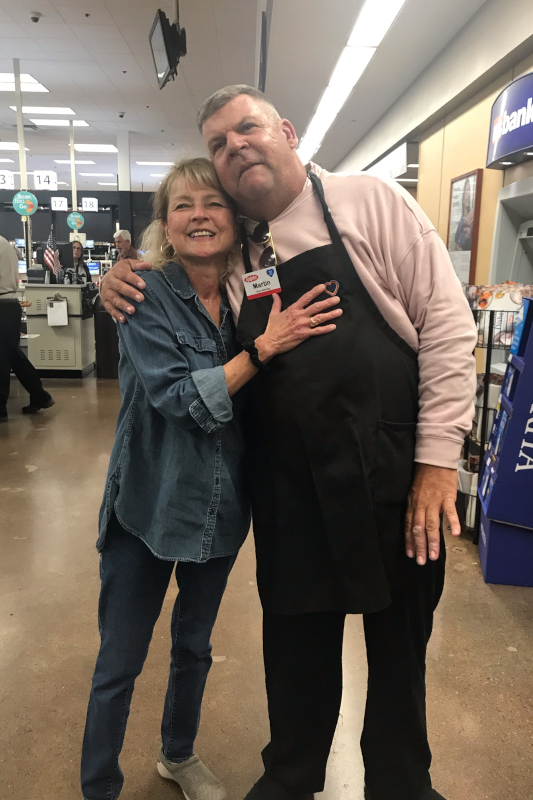 Martin and lady in a jean shirt at Ralphs hugging sideways and smiling at the camera