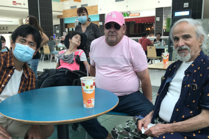 Martin and other members of the JNCS Self advocacy group sitting around a table at the mall