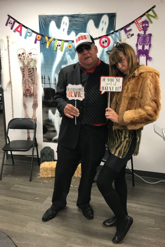 Martin in costume with a black suit and 'Boss' baseball cap posing with JNCS supervisor Lily at a Halloween party
